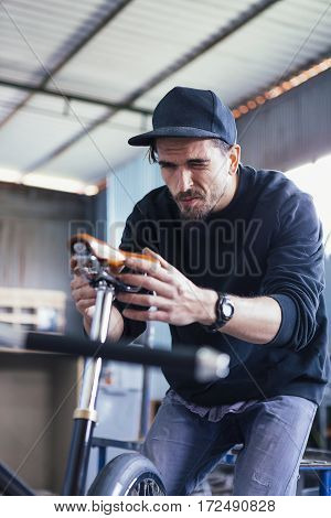 Close-up of craftsman in black cap squinting at bicycle seat