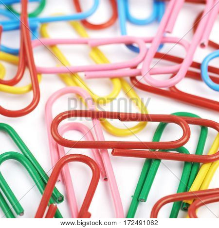 Surface coated with multiple colorful office clips over the white background as a shallow depth of field composition