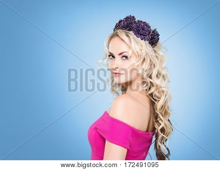 Beauty portrait of attractive blond girl with curly hair and a beautiful headband over blue background.
