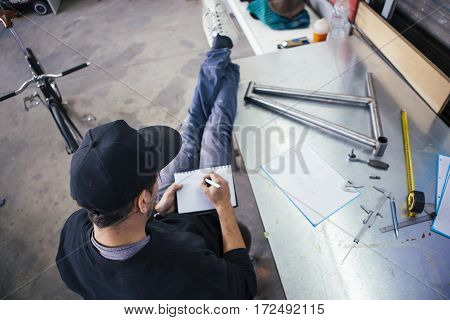 Unrecognizable craftsman taking notes while sitting on chair with legs on table
