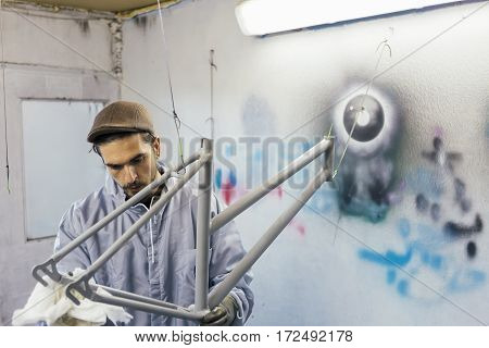 Bearded man in gloves cleaning bikes frame with white napkin