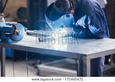 Unrecognizable worker welding bikes detail at the workshop