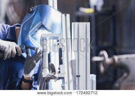 Unrecognizable man in blue mask welding iron bike detail
