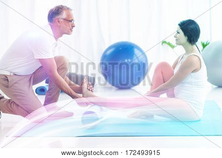 Physiotherapist giving physiotherapy to pregnant lady on exercise mat