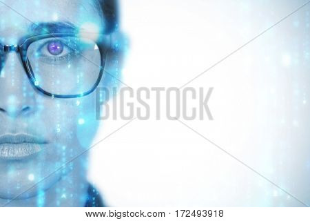 Woman wearing spectacles against digitally generated black and blue matrix