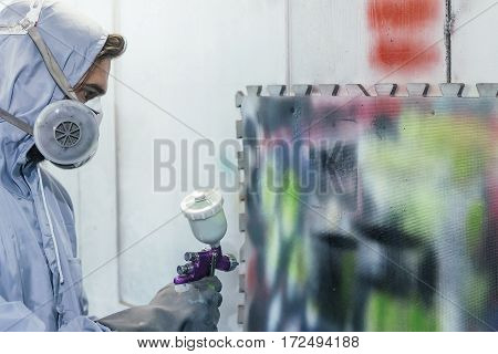 Side view of man in uniform and respirator paintinf on wall