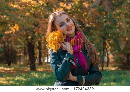 girl stands on the street bending head keeps leaves and smiles