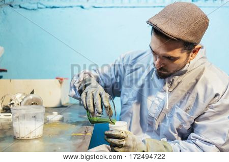 Bearded craftsman pouring green color to paint a bicycle
