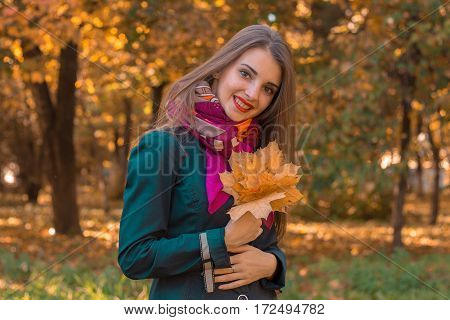 girl stands smiling in the Park and keeps the leaves from the trees