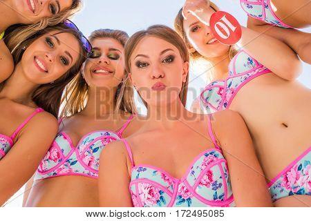 Five beautiful girls models standing round in bikinis. Down view.