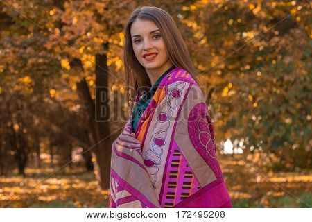 girl stands in the Park in a large scarf on the shoulders