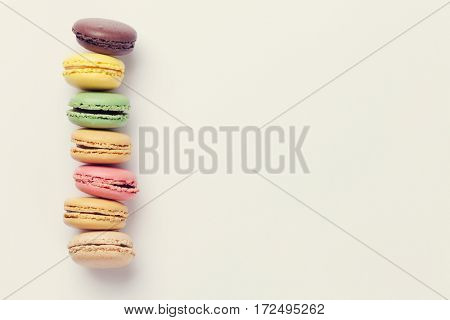 Colorful macaroons. Sweet macarons over color background with copy space