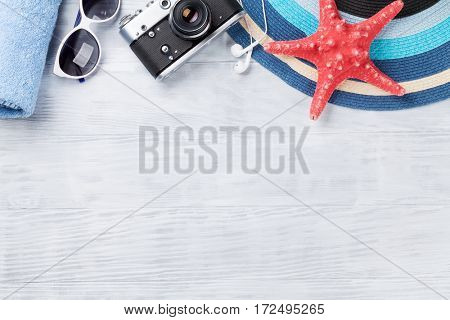 Beach accessories. Towel, camera, hat and sunglasses on wooden background. Top view with copy space