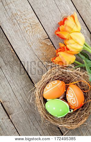 Easter eggs in nest and tulip flowers on wooden table. Top view with copy space