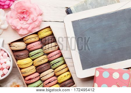 Colorful macaroons and blackboard. Sweet macarons in gift box on wooden table. Top view with copy space for your text