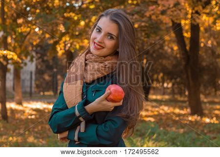 girl stands in the Park smiling and holding a Apple