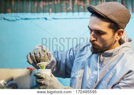 Bearded craftsman preparing green paint for bike frame