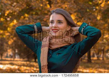 girl in a scarf in the park stands and raised her hands to her head