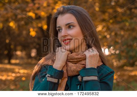girl stands on the street and keeps hands scarf