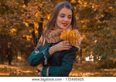 girl stands in the park looks away and keeps the leaves