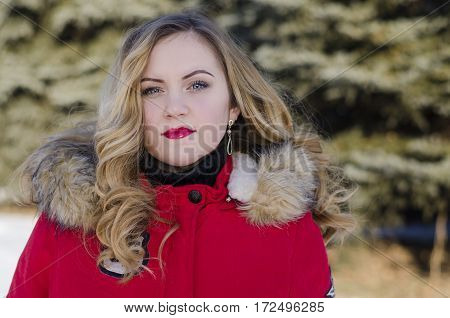 Portrait of a young girl in a red jacket on the background of fir trees