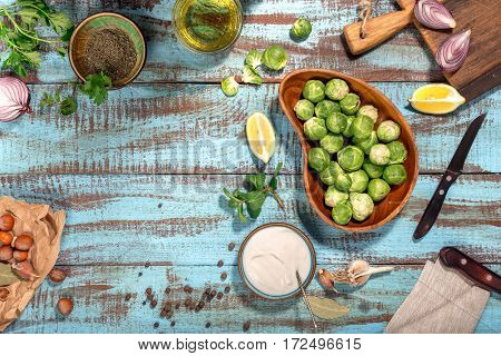 Brussels sprouts with ingredients for cooking tasty and healthy food on wooden table with copy space top view