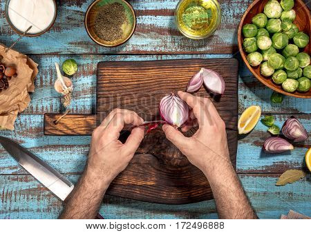 Man cooking a healthy food of brussels sprouts on a blue wooden table. Ingredients for healthy food top view. Rustic style