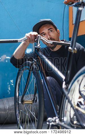 Close-up of professional bearded man looking at his bicycle