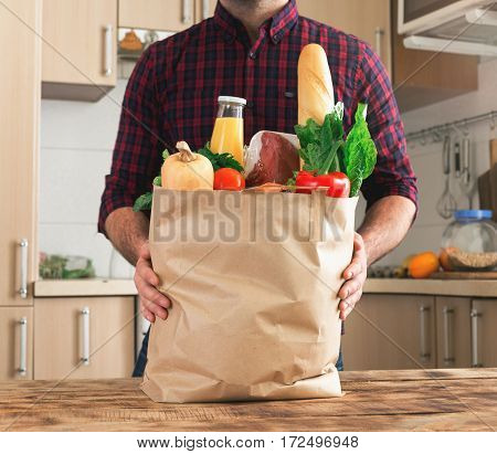 Man holding a paper bag full of healthy food on a wooden table in the home kitchen