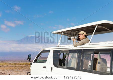 Professional photographer making shoot of Kilimanjaro mount aboard safari jeep, Kenya, Africa
