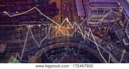 Stocks and shares against road in city at night