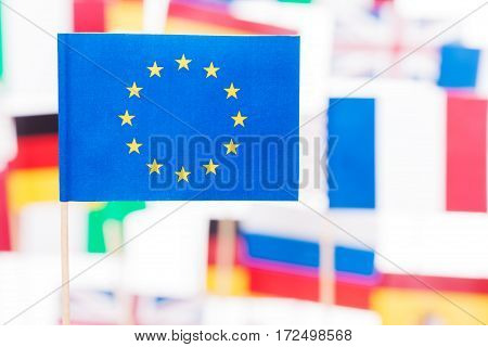 Close-up picture of small paper flag of European Union against flags of EU member-states