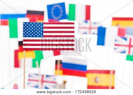Small flag of America against flags of European Union member-states and Russia