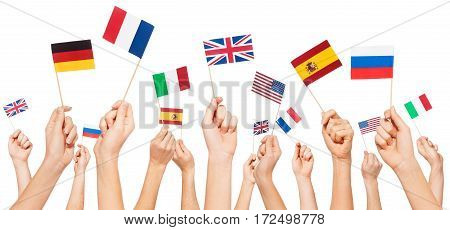 Hands holding small paper flags of USA and European Union member-states, isolated on white