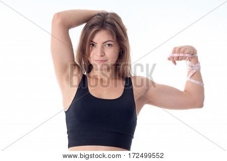 close-up of a beautiful slender athletic girl who smiles and shows his muscles and the other hand holding his head