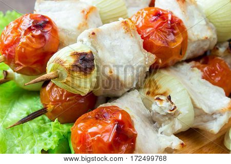Skewered on wooden sticks tasty pork meat and vegetables mix, on wooden background. macro