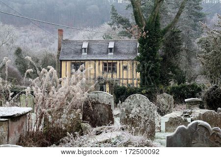 Medieval house near grave yard in winter , UK