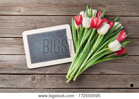 Colorful tulips bouquet and chalkboard on wooden background. Top view with space for your greetings
