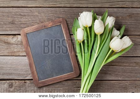 White tulips bouquet and chalkboard on wooden background. Top view with space for your greetings