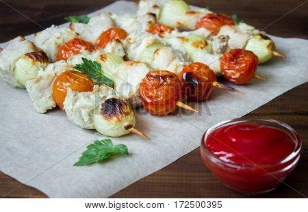 Skewered on wooden sticks tasty pork meat and vegetables mix, on wooden background