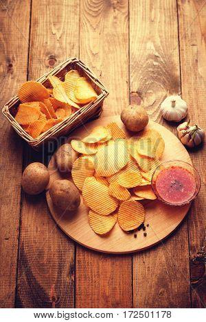 Crispy potato chips, potato and sauce on a wooden background