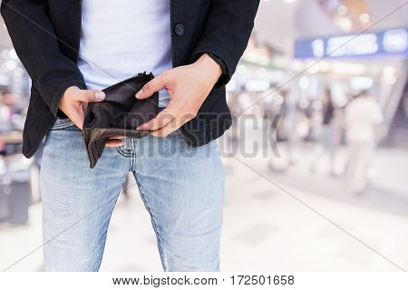 Man showing his empty wallet on blur shopping mall background.