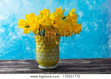 Bright yellow Narcissus flowers bouquet in a yellow glass vase Easter and spring concept copy space