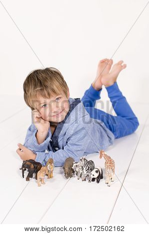 Boy with toy animals on the floor