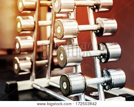 Stand with dumbbells in gym with hign contrast and monochrome color tone