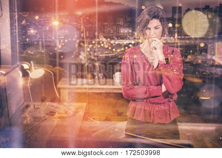 High angle view of illuminated cityscape against businesswoman looking at computer in office