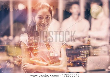 High angle view of illuminated cityscape against happy businesswoman standing with arms crossed