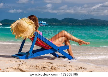 Woman in lounger on tropical beach at Thailand