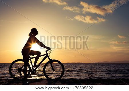Happy Woman With Bicycle Standing On The Beach