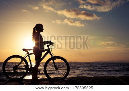 Happy teen girl walking on the beach at the sunset time